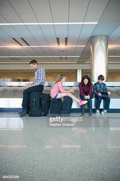 family at airport texting