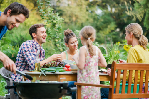 Family At Barbeque In A Garden