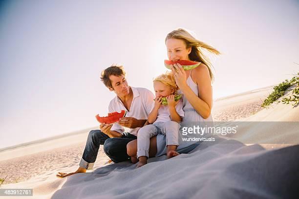 Famille manger la pastèque sur la plage