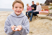 Family at beach with picnic smiling focus on boy with seashells