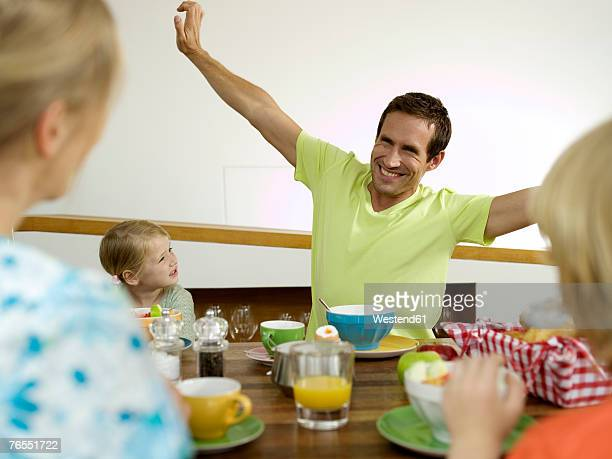 Family at breakfast table, man with arms outstretched