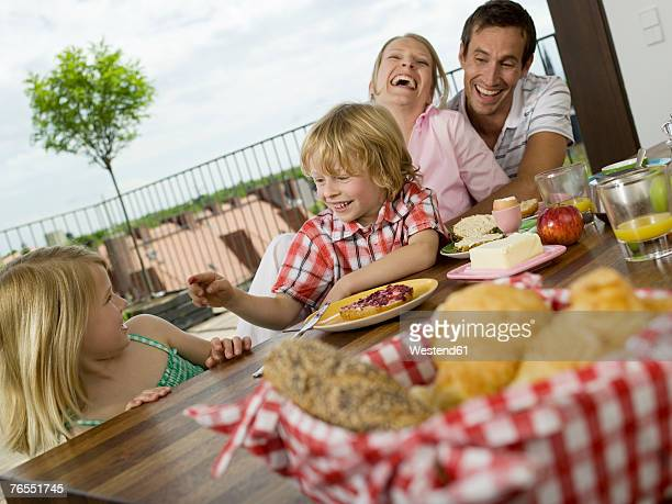 Parents with children (6-9) at breakfast table, smiling