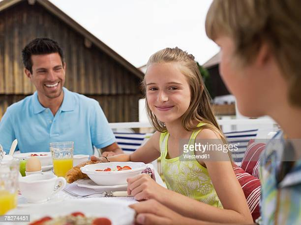 Father with daughter and son (10-13) at dinning table, smiling
