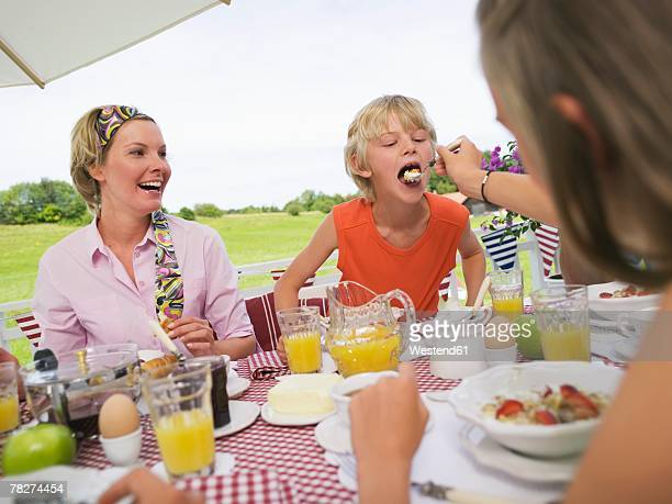 Mother with children (8-11) sitting at breakfast table, girl feeding boy