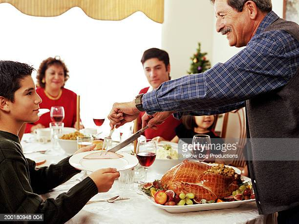 Family at dinner table, grandfather putting food on grandson's plate