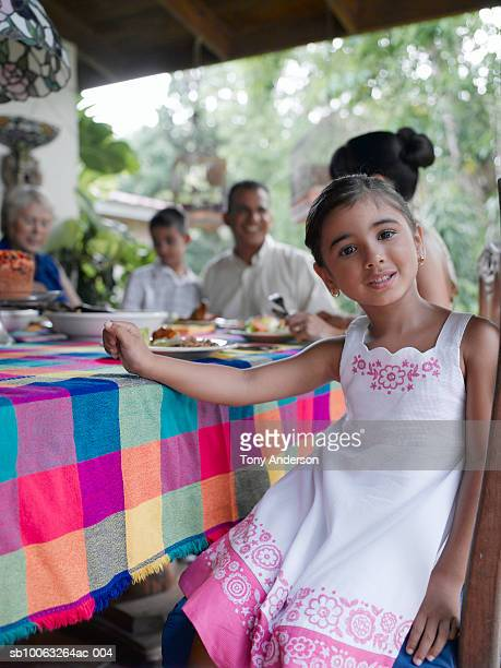 Family at dinning table, focus on girl (4-5) at foreground