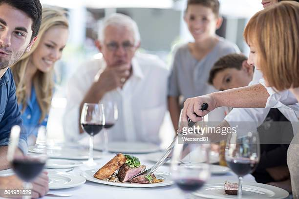 Family at family celebration looking at meat being served