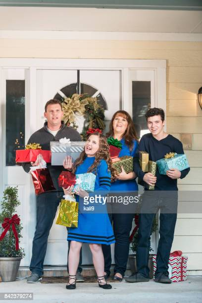 Family at front door carrying Christmas gifts