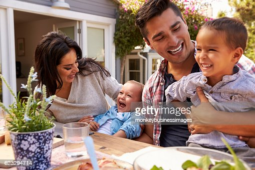 Family At Home Eating Outdoor Meal In Garden Together : Stock-Foto