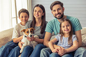 Beautiful young parents, their cute little daughter and son are looking at camera and smiling, sitting with their cute dog on sofa at home