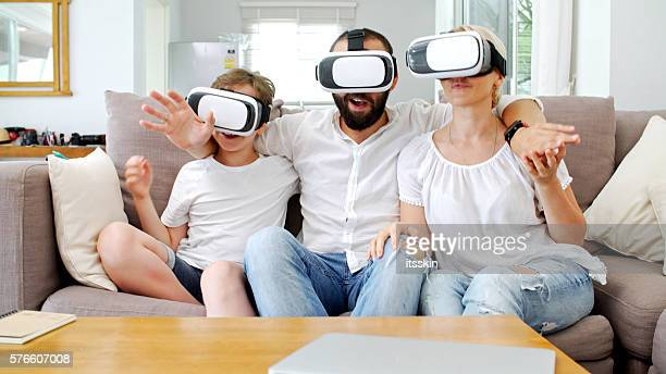 Family at home playing with virtual reality headsets. VR.