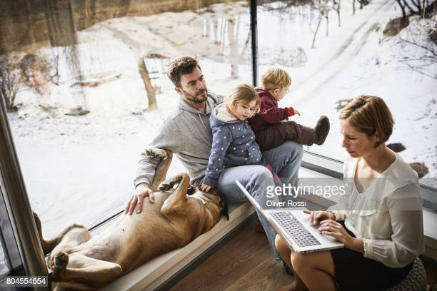 Family at home with mother using laptop