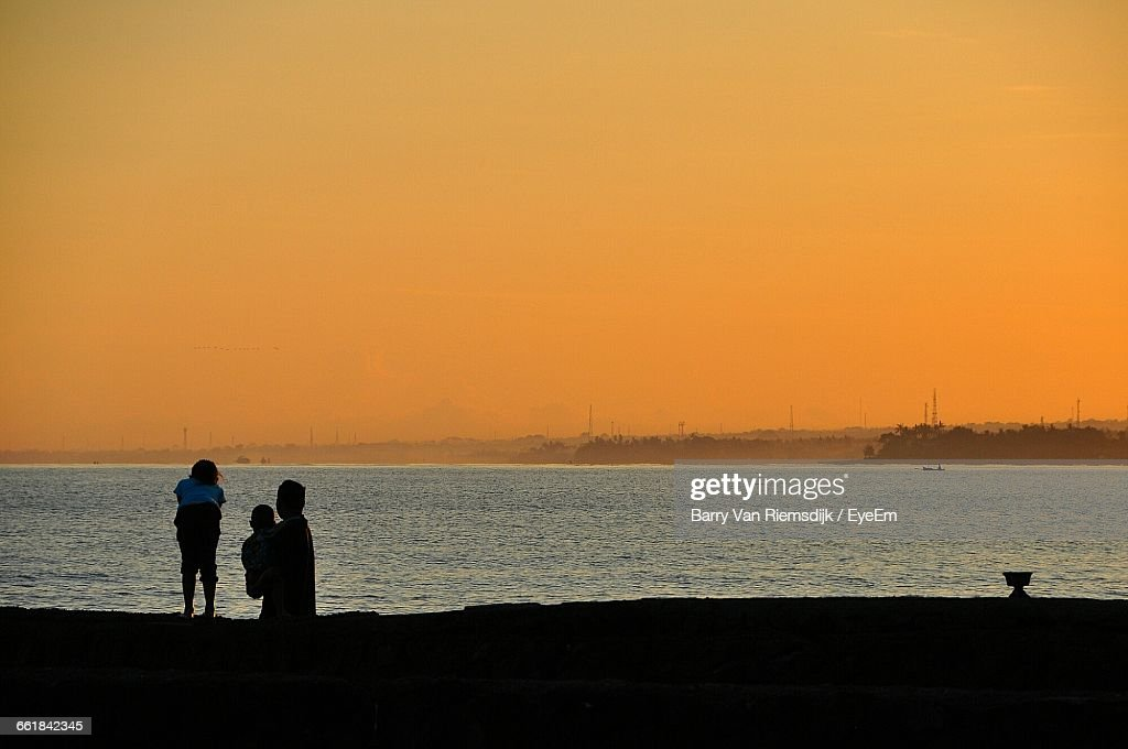 Family At Sea Shore Against Clear Sky During Sunset