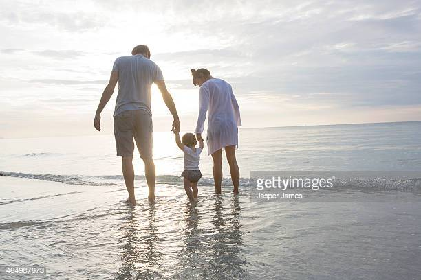 family at the beach,walking in the sea