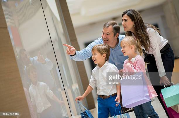 Família no shopping center, apontando para uma janela