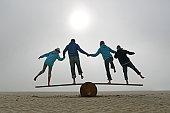 family balancing on beach