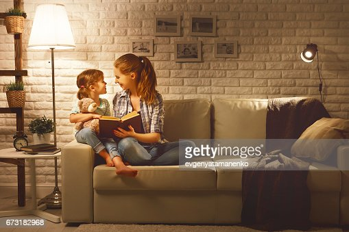 Family before going to bed mother reads to her child daughter book near a lamp in the evening : Stock Photo