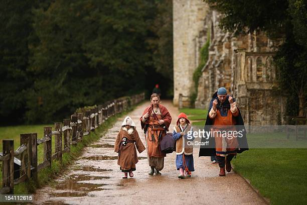 A family belonging to an historical reenactment group walk through Battle Abbey before the annual reenactment of the Battle of Hastings on October 13...