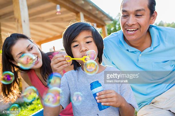 Family blowing bubbles outdoors