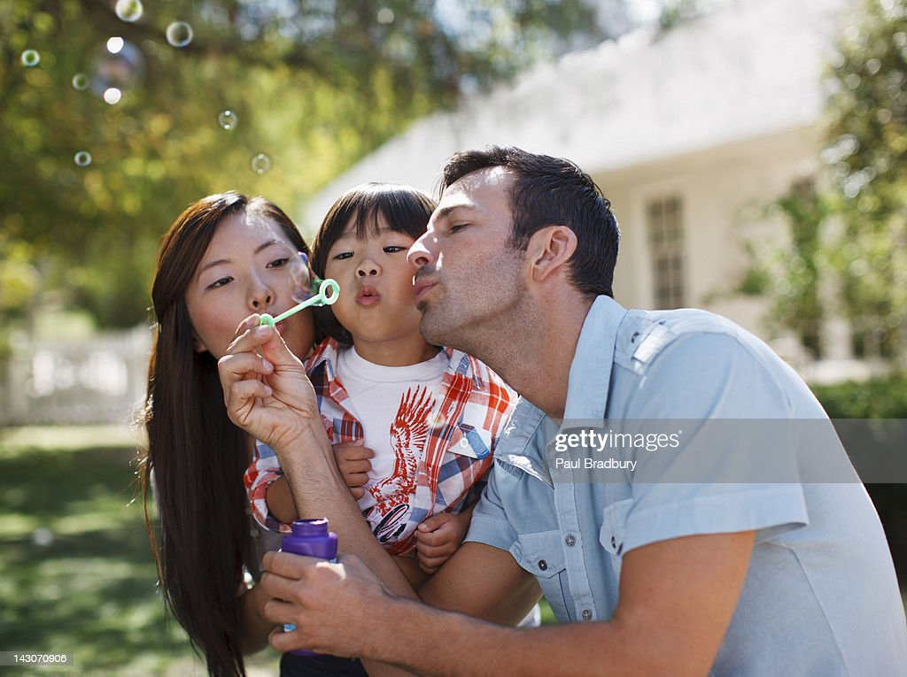 Family blowing bubbles together outdoors : Stock Photo