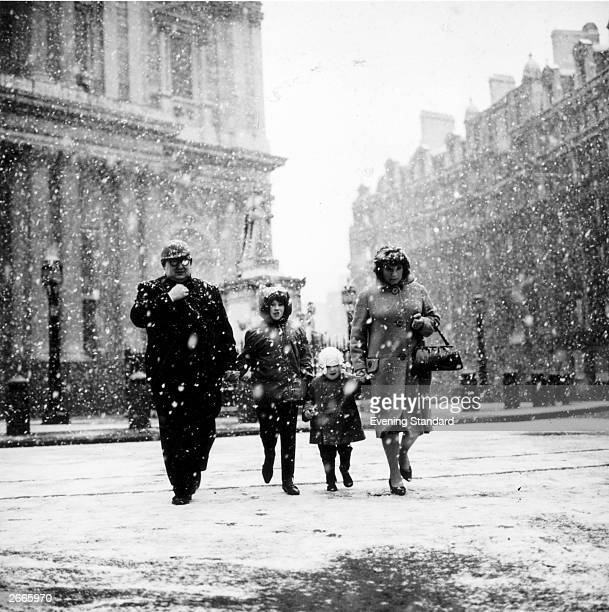 A family braving the weather as they walk past St Paul's Cathedral London during a snow storm