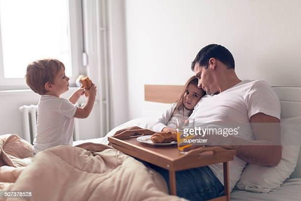 Famille petit déjeuner au lit