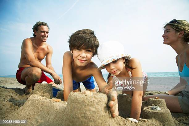 Family building sandcastles on beach, boy (8-10) smiling, portrait