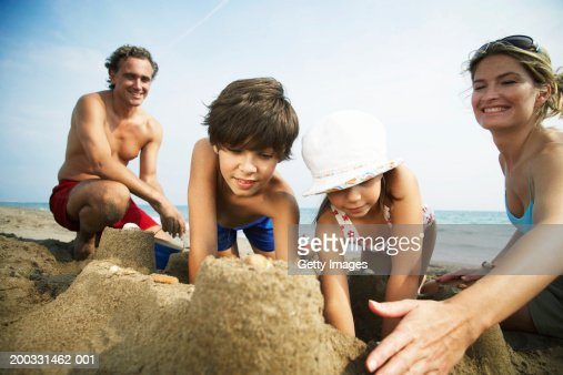 Family building sandcastles on beach, woman patting wall, close-up : Stock Photo