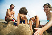 Family building sandcastles on beach, woman patting wall, close-up