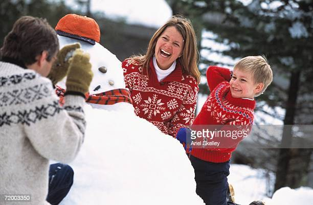 Family building snowman and laughing