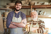 Father and son smiling and looking at camera in pottery