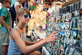 Family sightseeing Pisa. Teenage girl and her family are browsing and buying souvenirs at street market stand at Pisa, Tuscany, Italy. Nikon D810
