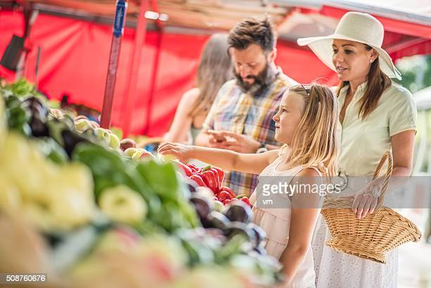 Family buying vegetables on outdoor stand