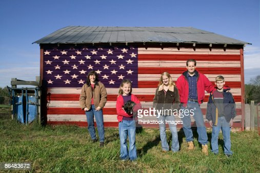 Family by barn with American flag