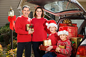 Family by car loaded with Christmas presents
