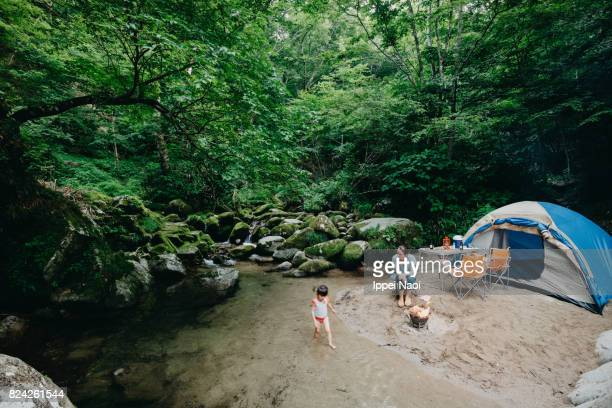 Family camping by forest stream, Ibaraki, Japan