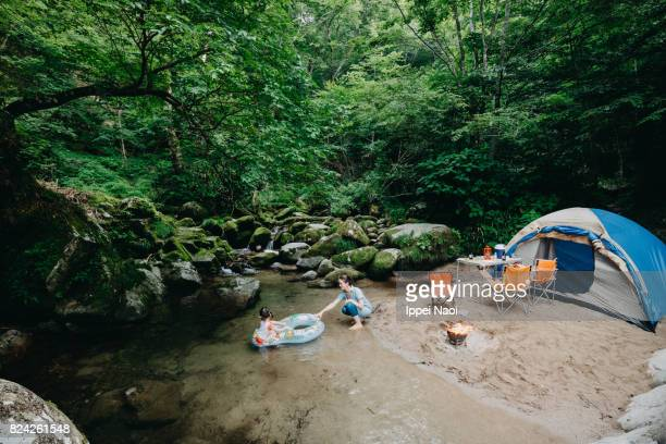 Family camping next to clear stream in forest, Japan