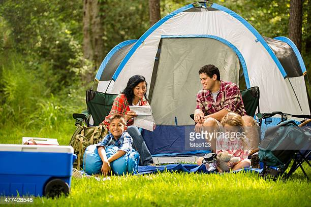 Family camping outdoors in forest. Tent, supplies. Summer vacation.