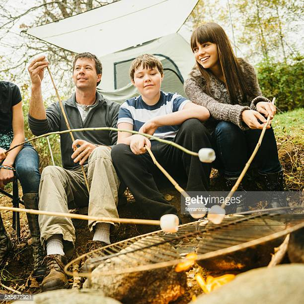 Familie Camping toast marshmallows am Lagerfeuer