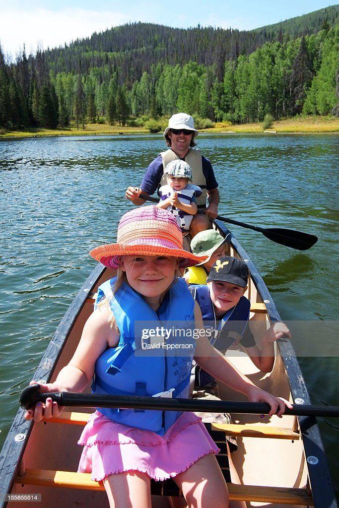 Family canoeing on lake in mountains : Stock Photo