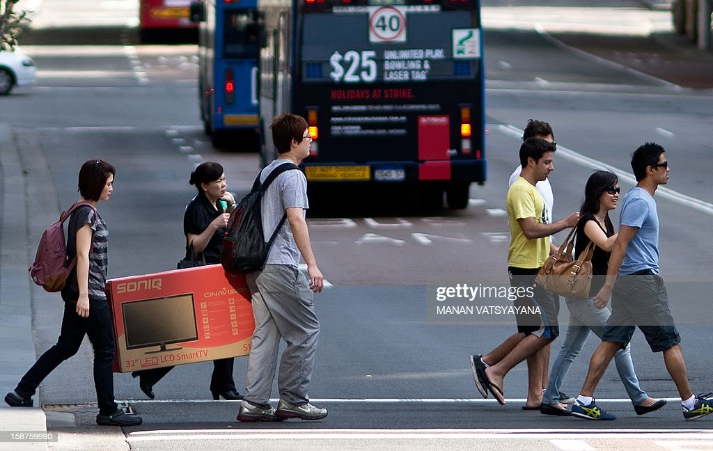 A family carries a television set across a street in Sydney on December 28, 2012. Shoppers are flocking the retail stores across the city to take advantage of post Christmas sales and discount promotions. AFP PHOTO / MANAN VATSYAYANA