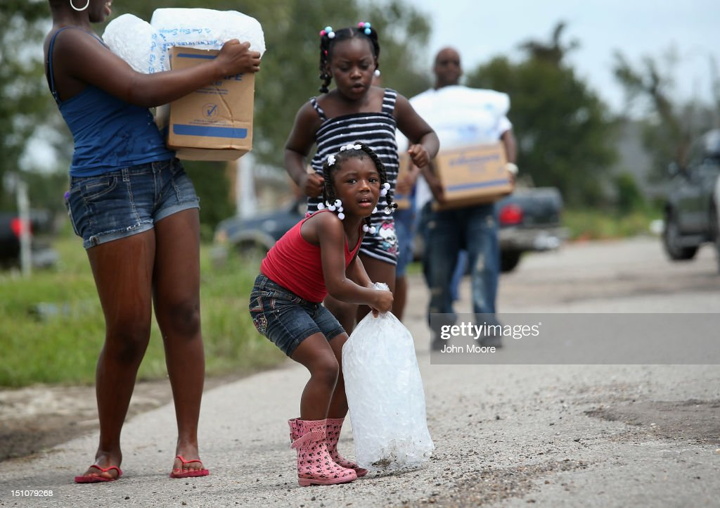 A family carries bags of ice and boxes of food from an aid distribution center for victims of Hurricane Isaac on August 31, 2012 in New Orleans, Louisiana. The center was one of three in New Orleans operated by the military, which handed out bags of ice, boxes of food and tarps to residents, many of whom still have no electricity due to the storm.