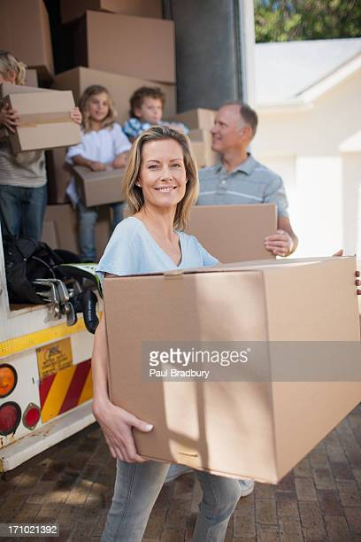 Family carrying boxes from moving van