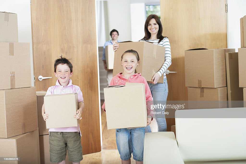 Family carrying boxes into new home : Stock Photo