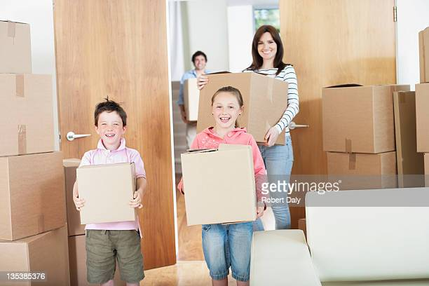 Family carrying boxes into new home