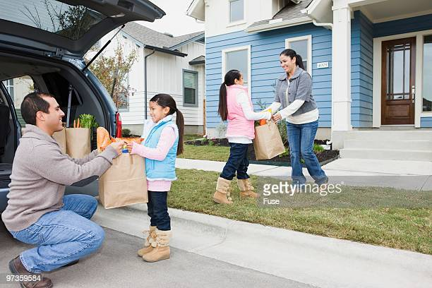 Family carrying groceries into the house