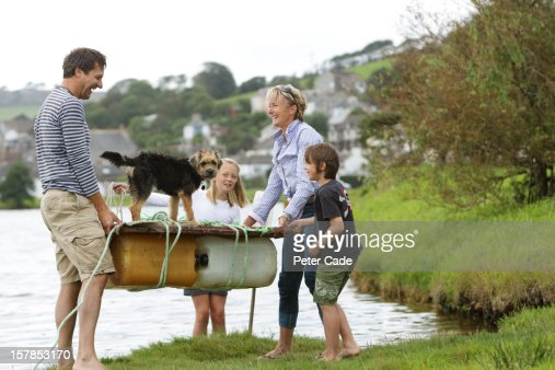 Family carrying home made raft into water : Stock Photo