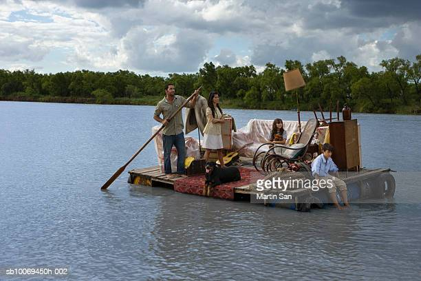 Family carrying house furniture in wooden raft