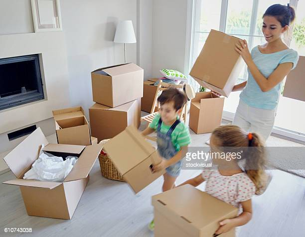 Family carrying large cardboard boxes into new home, portrait