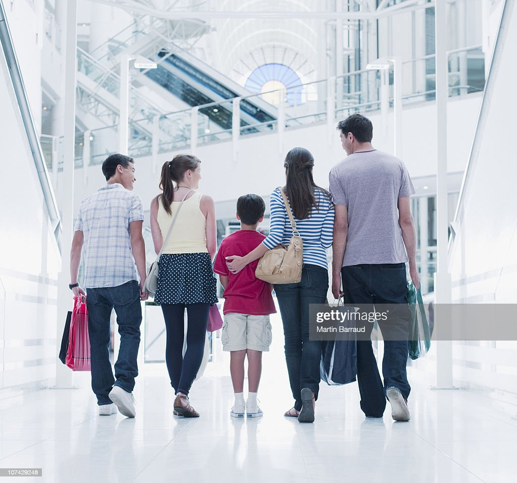 Family carrying shopping bags in mall : Stock Photo